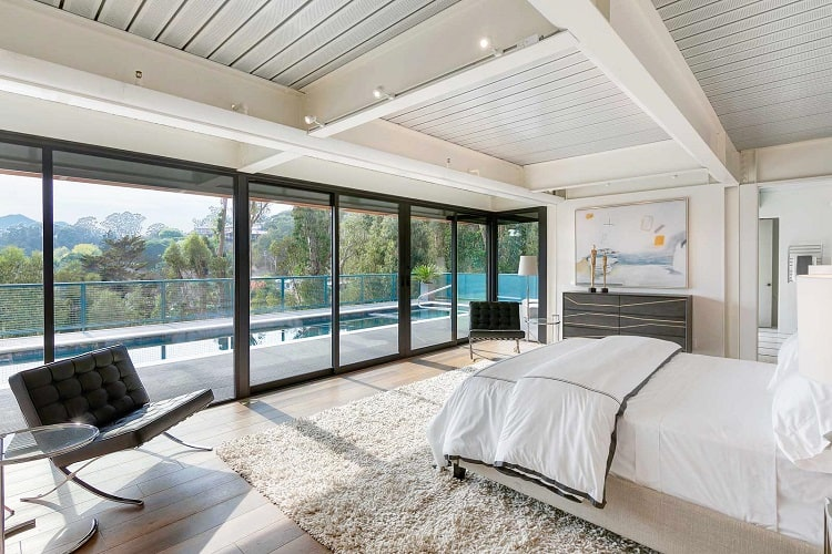modern bedroom with glass walls overlooking the pool